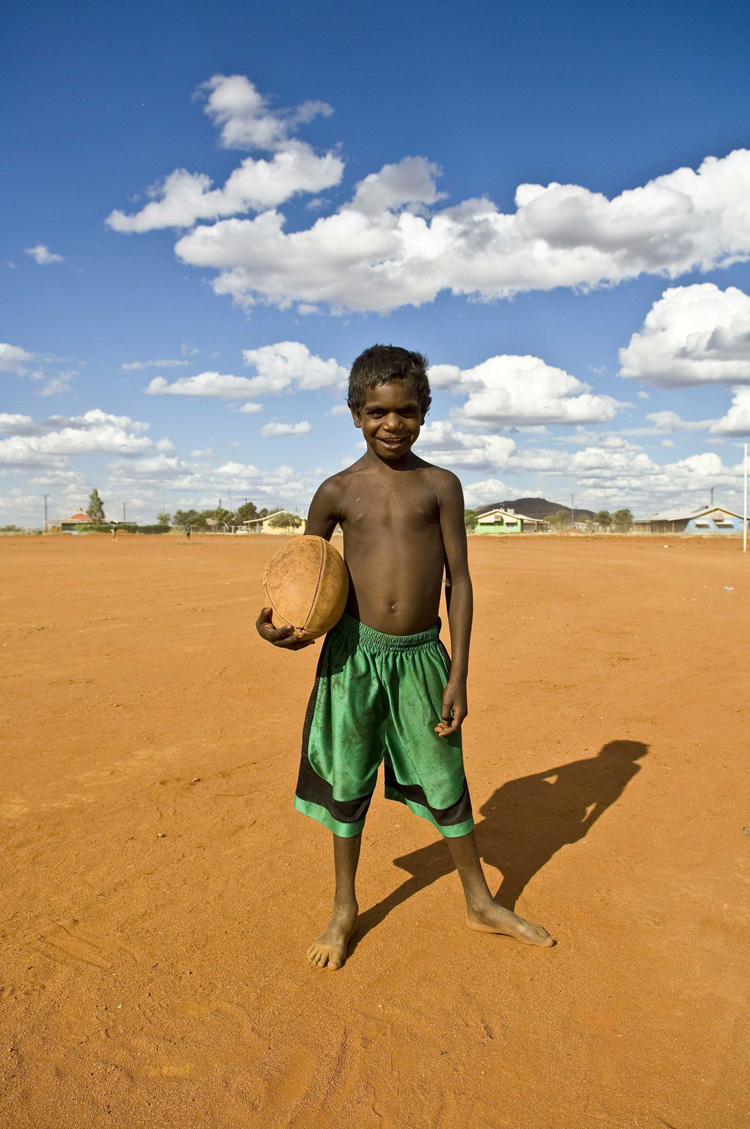 image of AARONTAIT-COPYRIGHTED-2014-5362 EDITORIAL DOCUMENTARY PHOTOGRAPHER PAPUNYA NORTHERN TERRITORY AUSTRALIA LANDSCAPE LIFE PEOPLE ART INDIGENOUS PINTUPI LURITJA PAPUNYA TULA FOOTY AFL PORTRAIT RED GREEN B